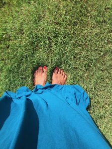 Brown skinned feet with red toenails on green grass.