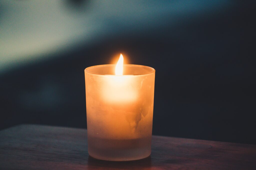 Photo of a candle in a darkened room. Decoration.